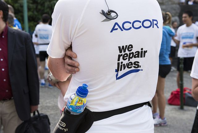 Rug van een loper gehuld in T-shirt met We Repair Lives-motto en logo van Accor.